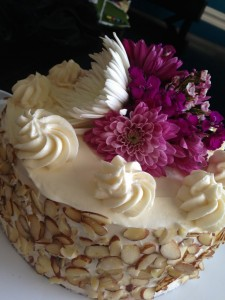 Mother's Day Cake covered in cream cheese frosting, topped with flowers and garnished with nuts.