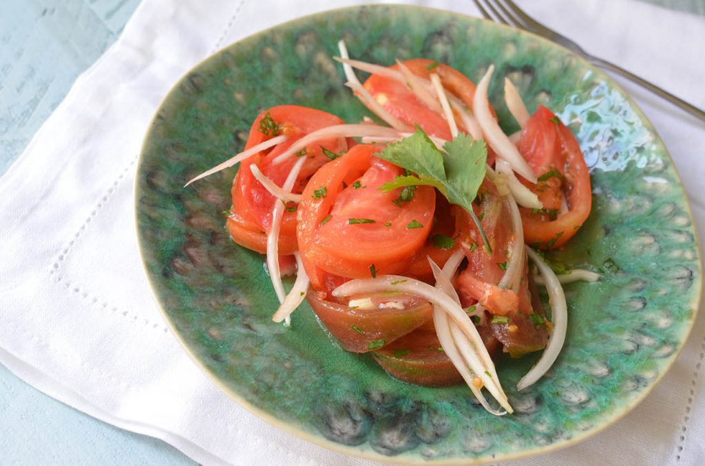 Ensalada Chilena! Mix your onion and tomato together gently, followed by your lime juice, olive oil, cilantro, and salt.