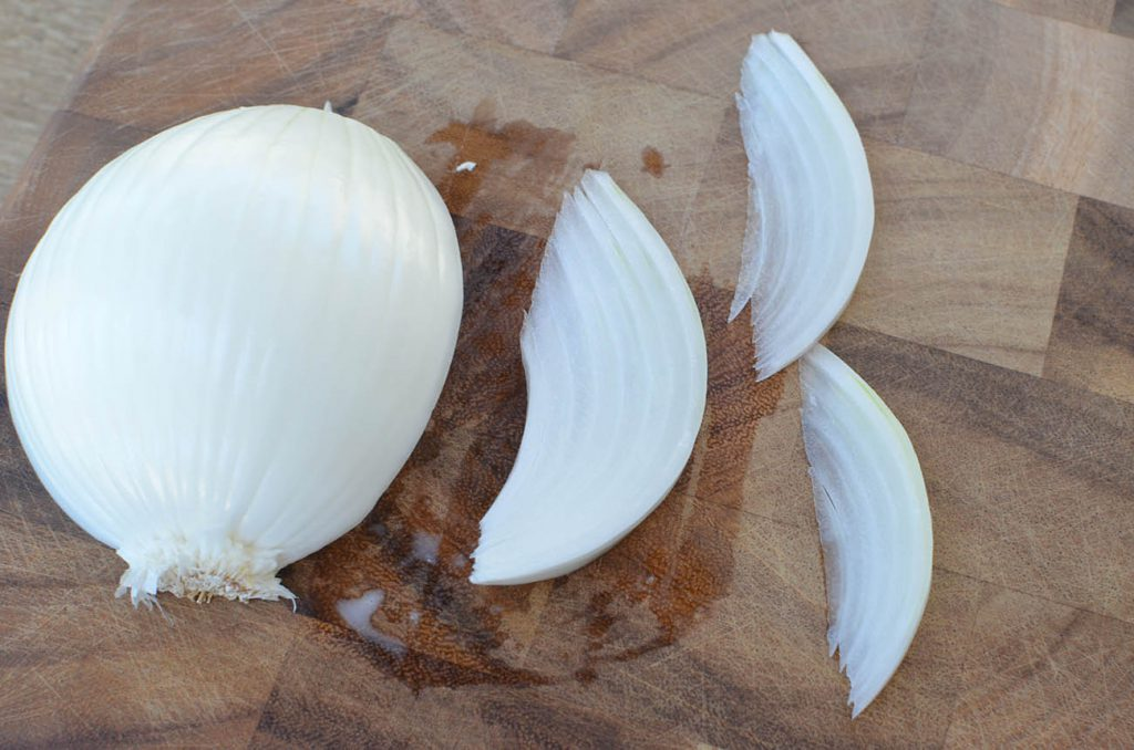 """feathering"" the onion. You will want to cut an onion in half, so that your knife spilts the root end in half. Remove the root end and slice from top to bottom."